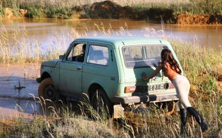 девушка толкает ваз 2121 из грязи